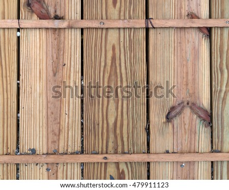 Close view of several pressure treated boards used for a footpath with stones between the grooves.