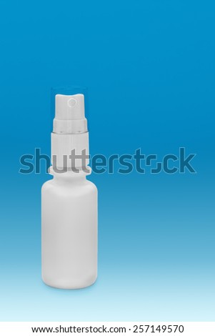 Close view of small white plastic bottle with sprayer in a blue background - stock photo