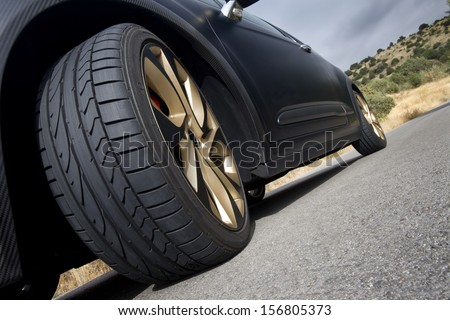 Close view of the wheel of a black sport car with the asphalt at foreground. Wheel.
