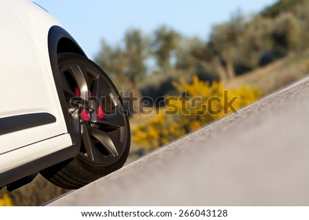 Close view of the wheel of a withe sport car on a road.  Wheel on a road.  - stock photo