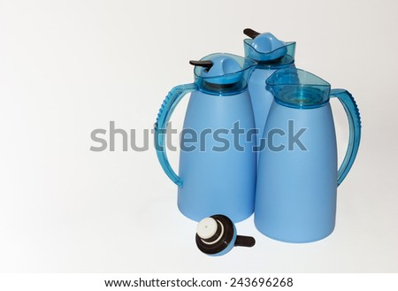 Close view of three blue thermoses in white background - stock photo