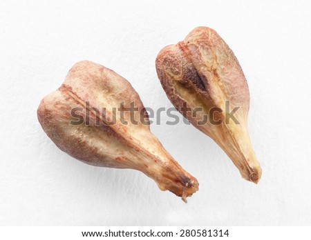 Close view of two dried grape seeds in a white background