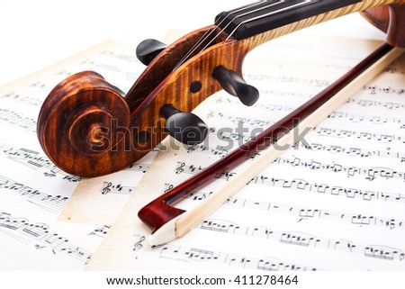 Close view of violin scroll and bow on musical sheet