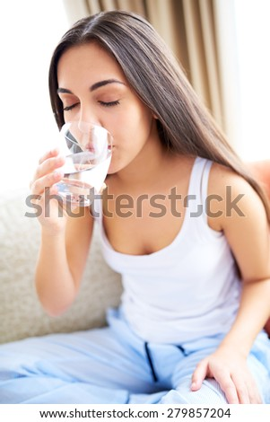 Close view of woman drinking glass of water with eyes closed. - stock photo