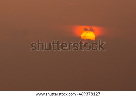Close View Of Yellow Disk Of Setting Rising Sun With Red Glow Around,