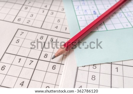 Close view on pencil on sudoku crosswords. Popular game with numbers. - stock photo