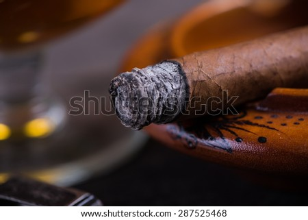 close view on smoking cuban cigar with ash - stock photo