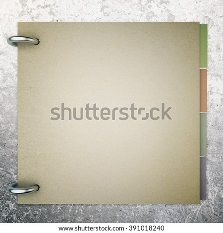 Closed blank notepad with colorful stickers inside on concrete background. Mock up - stock photo