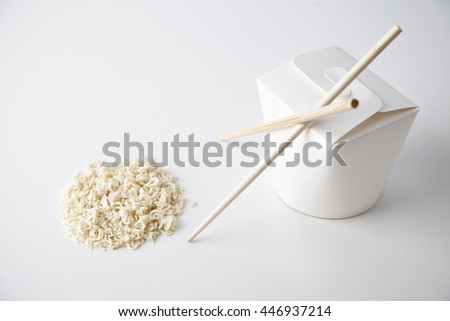 Closed blank takeaway noodles box with chopsticks near dry pasta in circle shape isolated on white close focus commercial presentation mockup - stock photo