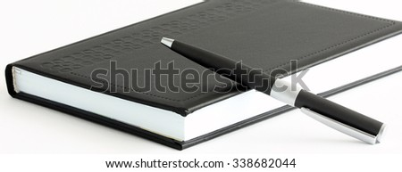 Closed book with a pen isolated on white - stock photo