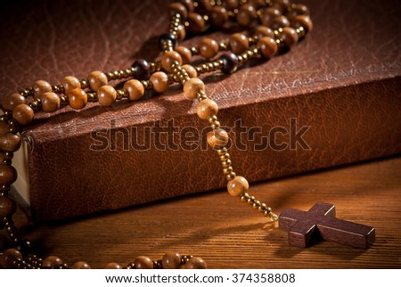 closed book with rosary on the wooden desk - stock photo