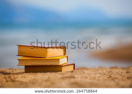 Closed books on a beach - stock photo
