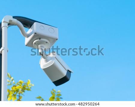 closed-circuit camera on blue clouds background,