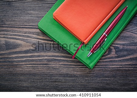 Closed diary books ball-point pen on vintage wooden board education concept. - stock photo