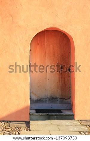 closed door, mediterranean facade with terracotta colored plastering - stock photo
