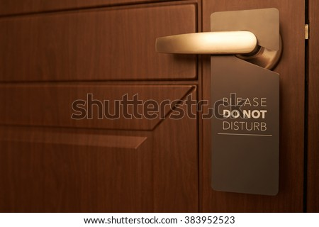 Closed door of hotel room with please do not disturb sign