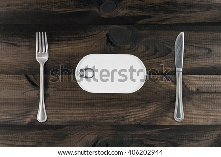 Closed easy open fish can with the pull tab and metal fork and butter knife on wooden table - stock photo