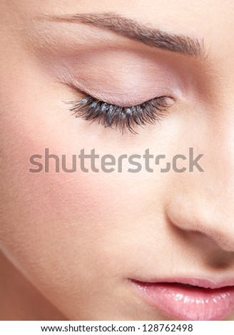 Closed eye of young beautiful woman with day makeup eye shadows - stock photo