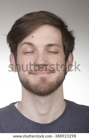 Closed eyes, not looking, portrait of caucisan young man in 20s. Head and shoulders shot, face close up. Shallow depth of field. - stock photo