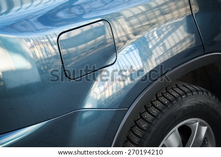 Closed fuel tank flap. Modern blue car closeup fragment with shallow DOF and selective focus - stock photo