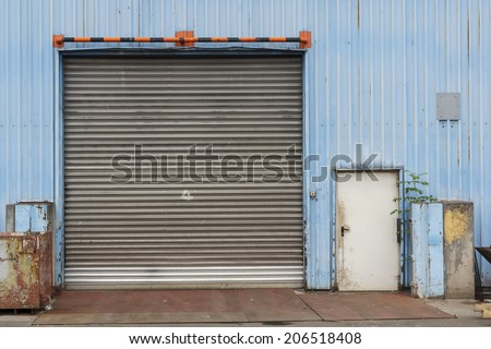 Closed gate in blue metal shed at industrial facility. - stock photo