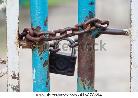 Closed gates with padlock and iron chain. metallic textures, shabby turquoise paint surface. macro view. Security concept with closed iron gate, vintage lock. soft focus - stock photo