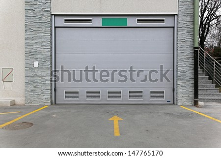 Closed gray garage  door entrance in building - stock photo