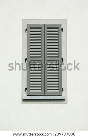 Closed green window on white wall background
