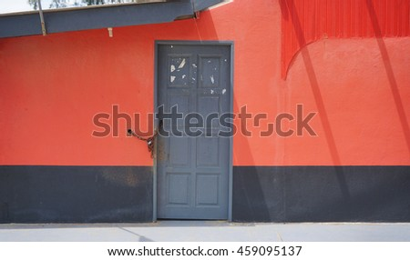 Closed grey door on red and wall background