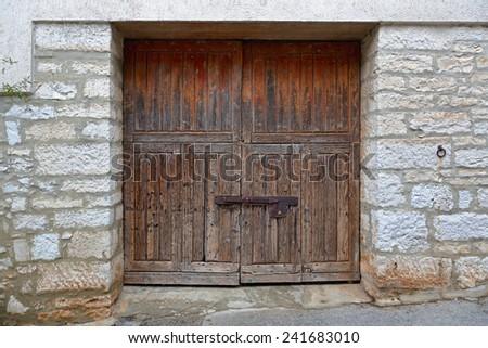 Closed grunge garage door at stone house - stock photo