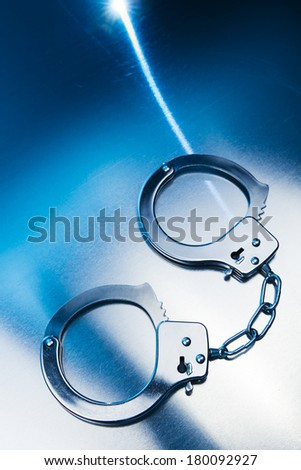 Closed handcuffs, Security concept on metallic background