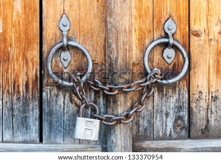 Closed lock with a chain on an old wooden door - stock photo