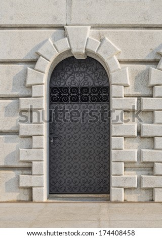 closed metal door on ancient wall, thailand - stock photo