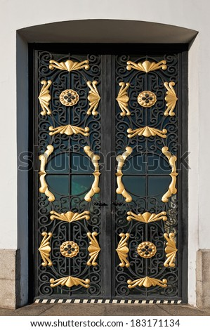closed metal door with decorative wrought-iron grille - stock photo