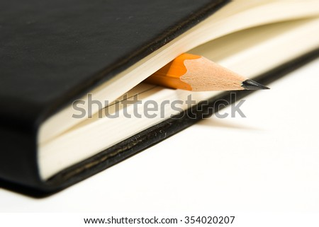 Closed notebook with a blank sheet and pencil on over white