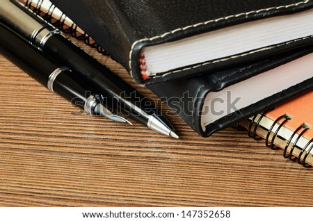 Closed notebooks and pens on wooden table