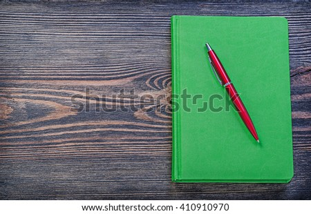 Closed notepad pen on vintage wood board copy space. - stock photo