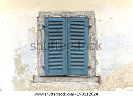 Closed old blue window shutters on a weathered plaster wall    - stock photo