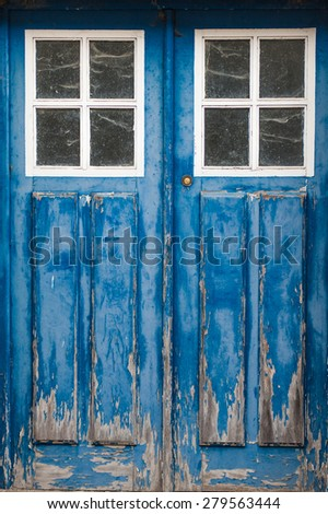 Closed old blue wooden vintage grungy door with two windows