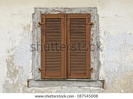 Closed old brown window shutters on a weathered plaster wall    - stock photo