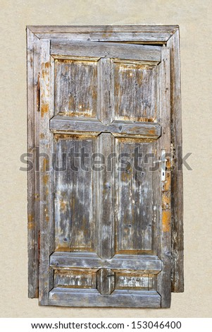 closed old wooden weathered door in a grout wall with cross design. - stock photo