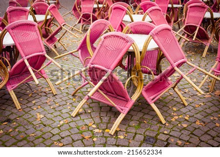 Closed outdoor cafe terrace with pink chairs. Vintage orange toning applied - stock photo