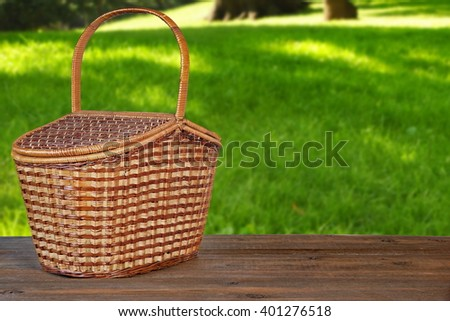 Closed Picnic Basket Or Hamper On  The Brown Rustic Wooden Table Or Bench In Park Or Garden Front View, Copy Space - stock photo