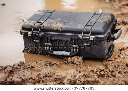 Closed plastic black protector case lying  on the water and dirt