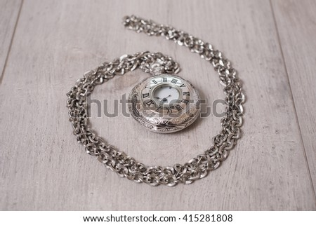 closed pocket watch lying on a light wooden background, arrow on the clock, arrows on pocket watches show time of day, dial with roman numerals, shiny metal clocks   - stock photo