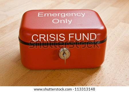 Closed red cash tin marked  Crisis Fund - Emergency Only - stock photo