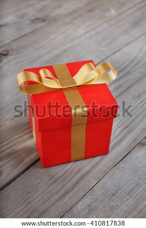 closed red gift box with gold ribbon on the wooden table - stock photo
