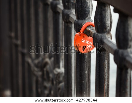 Closed red padlock in the form of heart locked on bridge. - stock photo