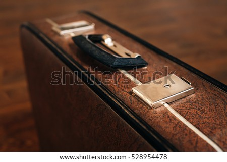 Closed retro suitcase on the wooden floor.