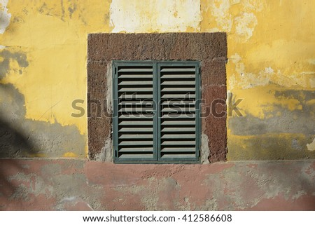 Closed shutters on window in weathered painted wall in old town of Funchal, Madeira, Portugal